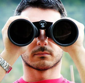 Photo of a man looking through binoculars, signifying the importance of looking ahead in your college search and what colleges are looking for in students. good colleges