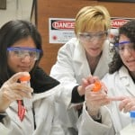 3 women wearing laboratory dress and eye protection.