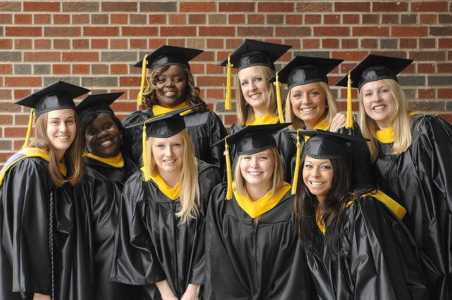 Graduating college students smiling for a group photo.