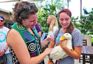 Two college students holding a duck at a campus event.