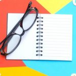 A pair of glasses sitting on top of a journal.