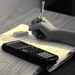 Student doing math homework with calculator and textbook.