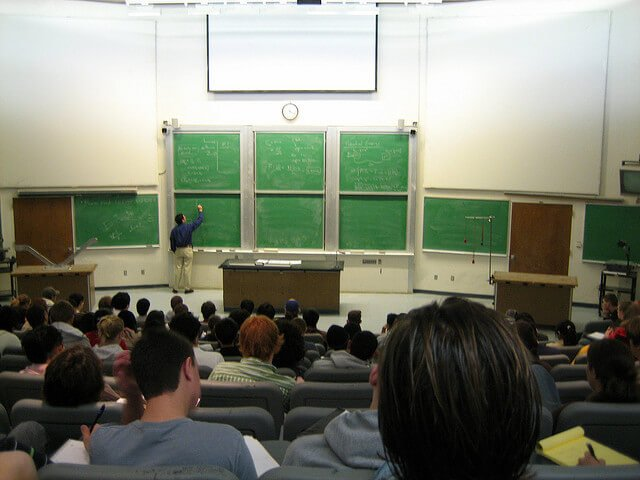 Students sitting a classroom while a professor lectures.