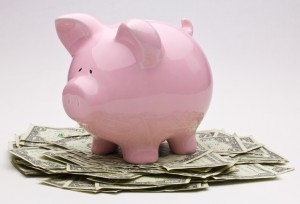 Pink piggy bank sitting on a pile of money.