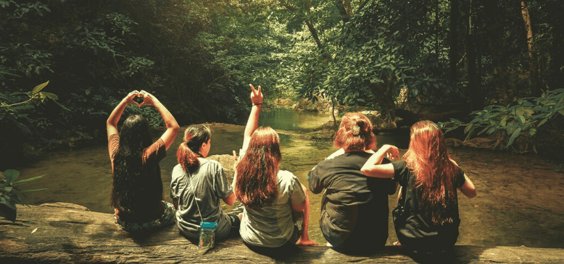 Five students sitting together on a log over a river.