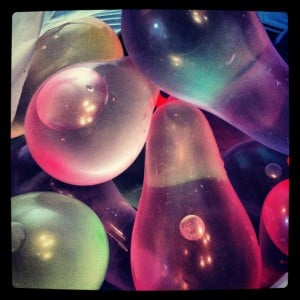 Colorful water balloons on top of each other.