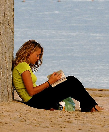 Photo of a girl reading a book on the beach.