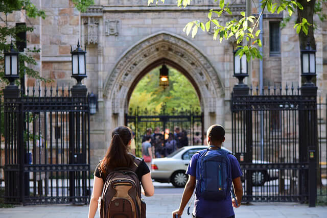 Two students walking towards Yale University's gate.