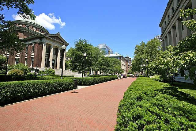 Students walk down red brick pathway at Columbia University's campus.
