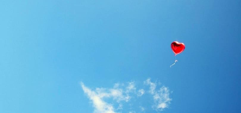 A red heart balloon floating against a blue sky.