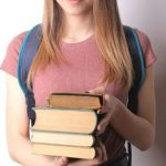 A student holding a stack of books with both hands.