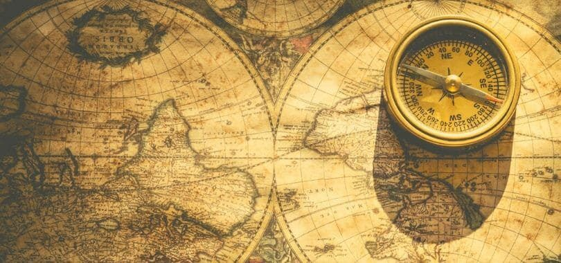 A compass sitting on a map of the world.