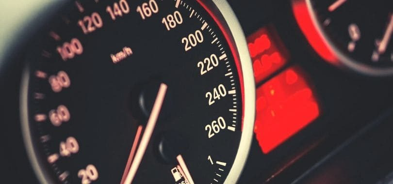 A black and red speedometer with a red light next to it.
