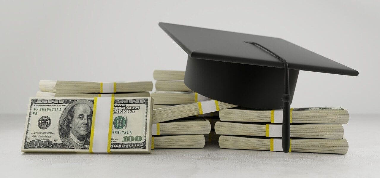 A stack of bills with a graduation cap sitting on top.