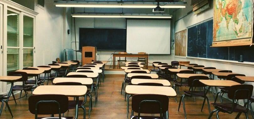 Uma sala de aula vazia com um quadro negro, bem como secretárias beges e castanhas.
