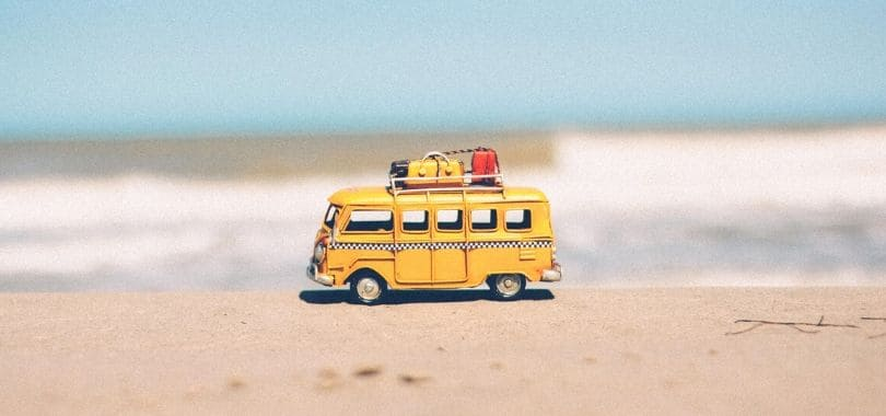 A small, yellow toy beach van at the beach.