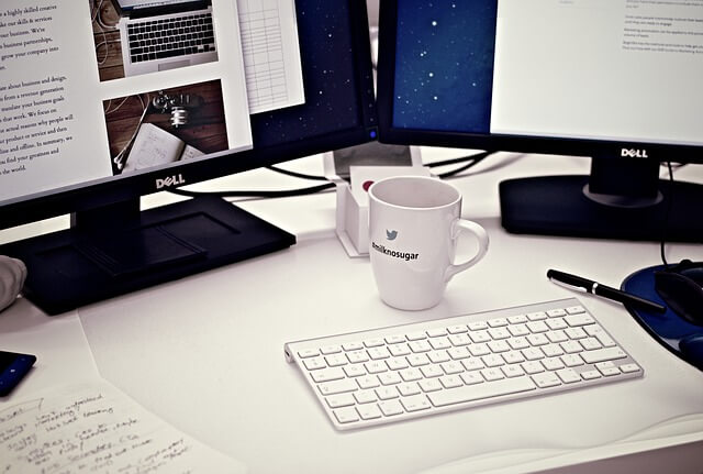 Dual Dell monitor on a desk with white coffee cup.