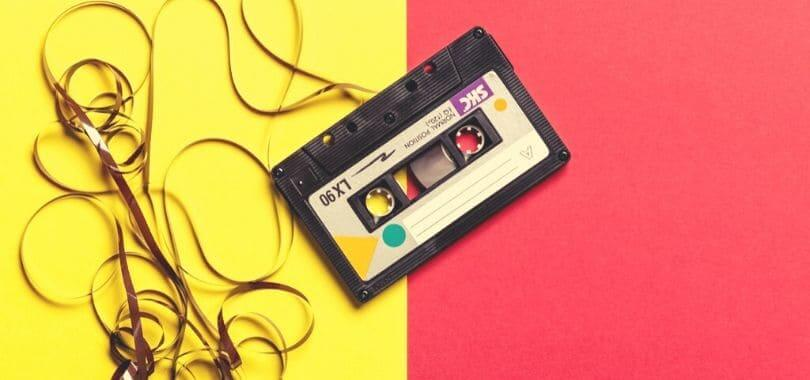 A cassette tape with the tape pulled out, against a yellow and red background.