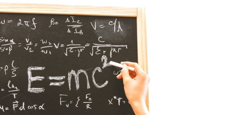 A person writing math formulas on a chalkboard.