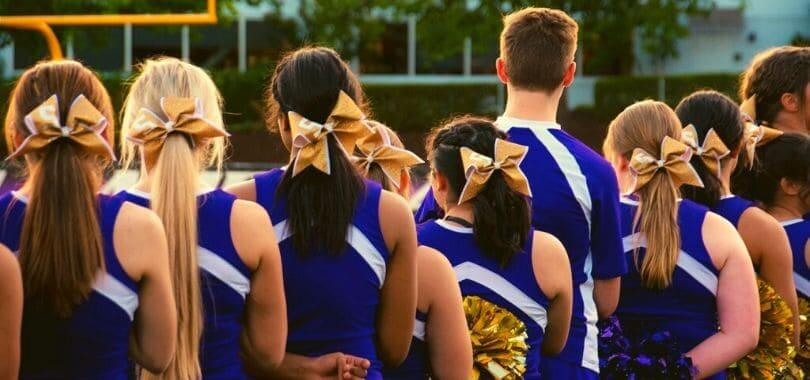 Cheerleaders in a blue uniform lined up.