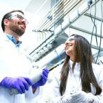 A group of scientists in white lab coats talking to each other.
