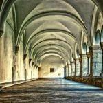 An empty hallway inside of a monastery.