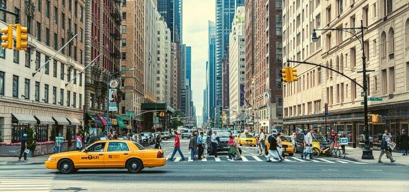Downtown New York with people crossing a street.