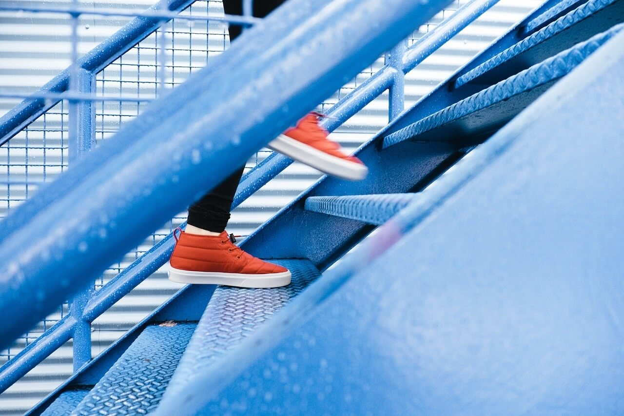 A person is wearing red shoes going up in a blue stair.