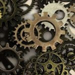 Different sizes and colors of gears in a pile.