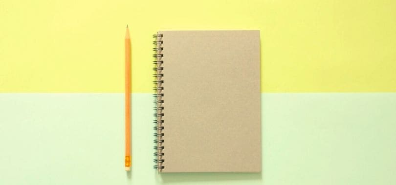 A pencil and notebook against a yellow and green background.