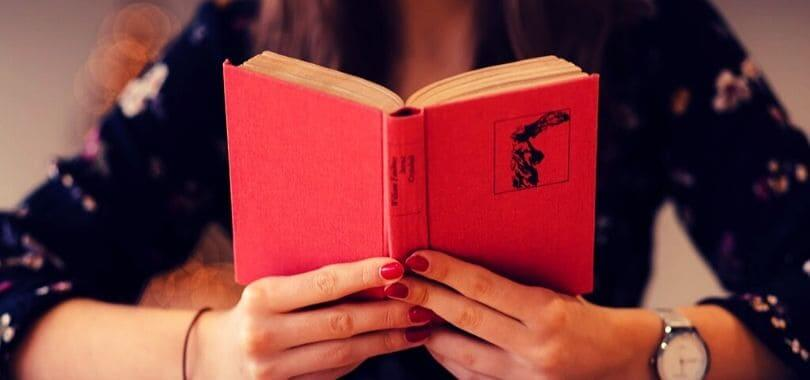 A person reading a red book.