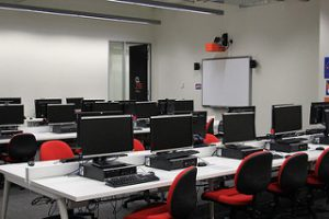 Computer laboratory with red chairs and desktops.