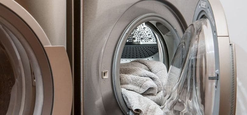 A silver washing machine with white towels inside the drum.
