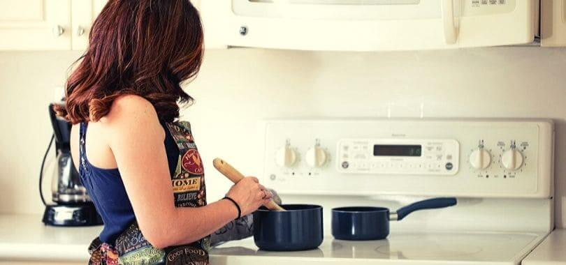 A person at a stove stirring a pot.