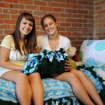 Two college roommates meeting for the first time and sitting in a bed inside a dorm room.
