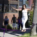 A girl walking on a purple tightrope that's tied to two trees.
