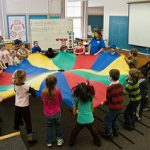 Kids gather around the big color wheel fabric and holding it.