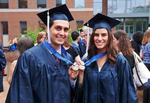 Two graduating honors students wearing blue robes holding up their medals.
