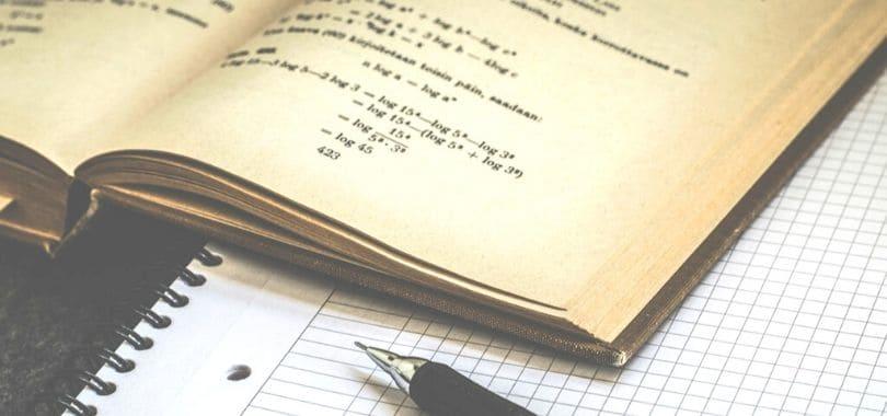 A math textbook open on top of a notebook.