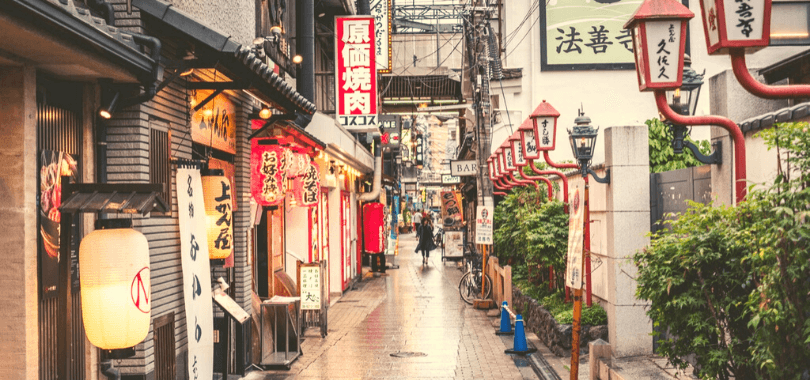 A person walking down a street filled with shops.