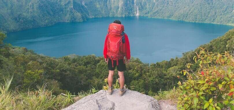 College student standing on top of a rock overlooking a lake.