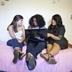 3 female students sitting on a purple bed and talking. The girl at the center is holding a laptop.