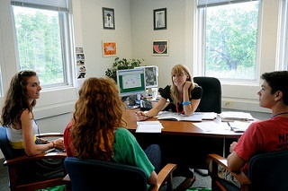 Three students meeting with their academic advisor inside her office.