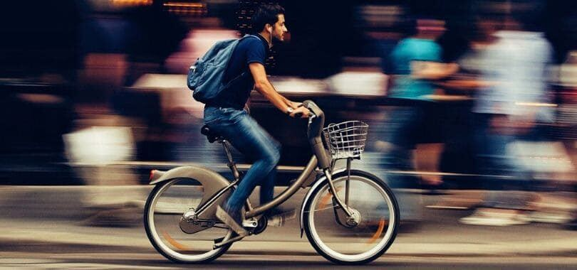A student riding a bicycle down a street.