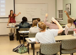 Students participating in a college class by raising their hands to answer the professor.