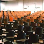 An empty lecture hall filled with brown desks.