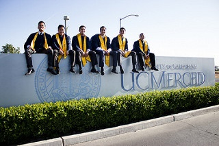 Students in graduation gowns sitting atop of the entrance sign at UC Merced.