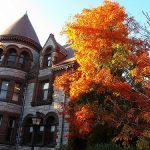 The Department of Applied Mathematics building with an autumn tree on the side at Brown University.