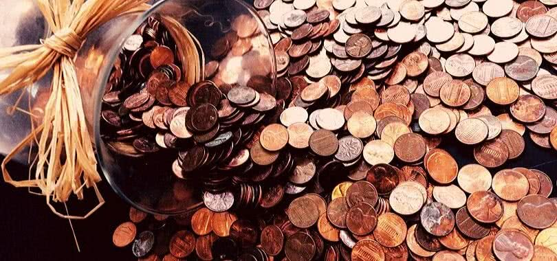 A coin jar with pennies and dimes spilling out of it.