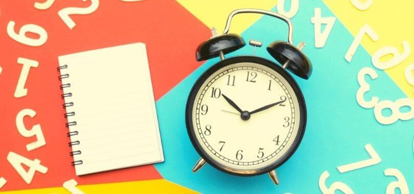 A black and white alarm clock next to an open notebook.